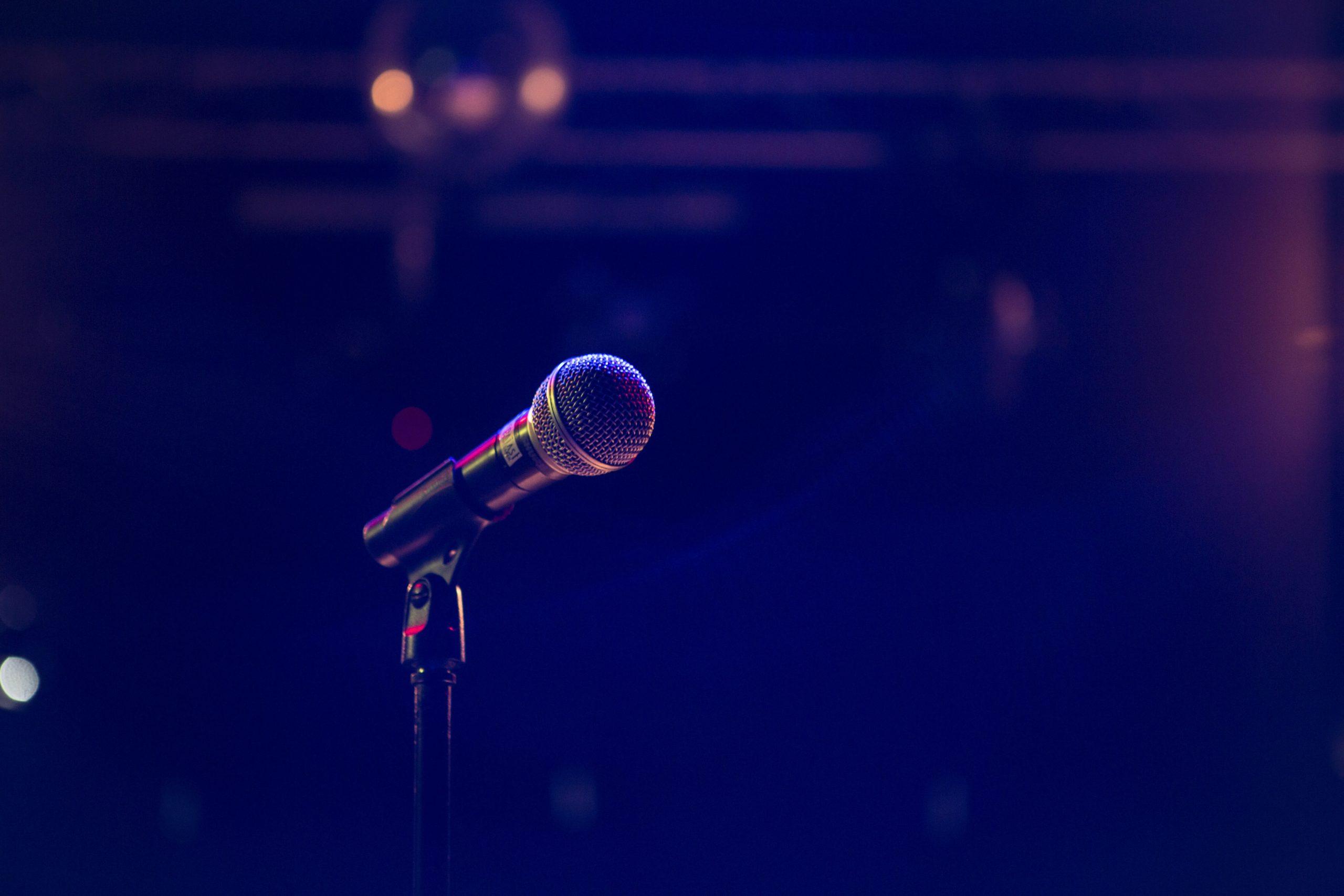 Microphone on a dark stage. - Lyssa-Fee Crump on You BetterWerk podcast/