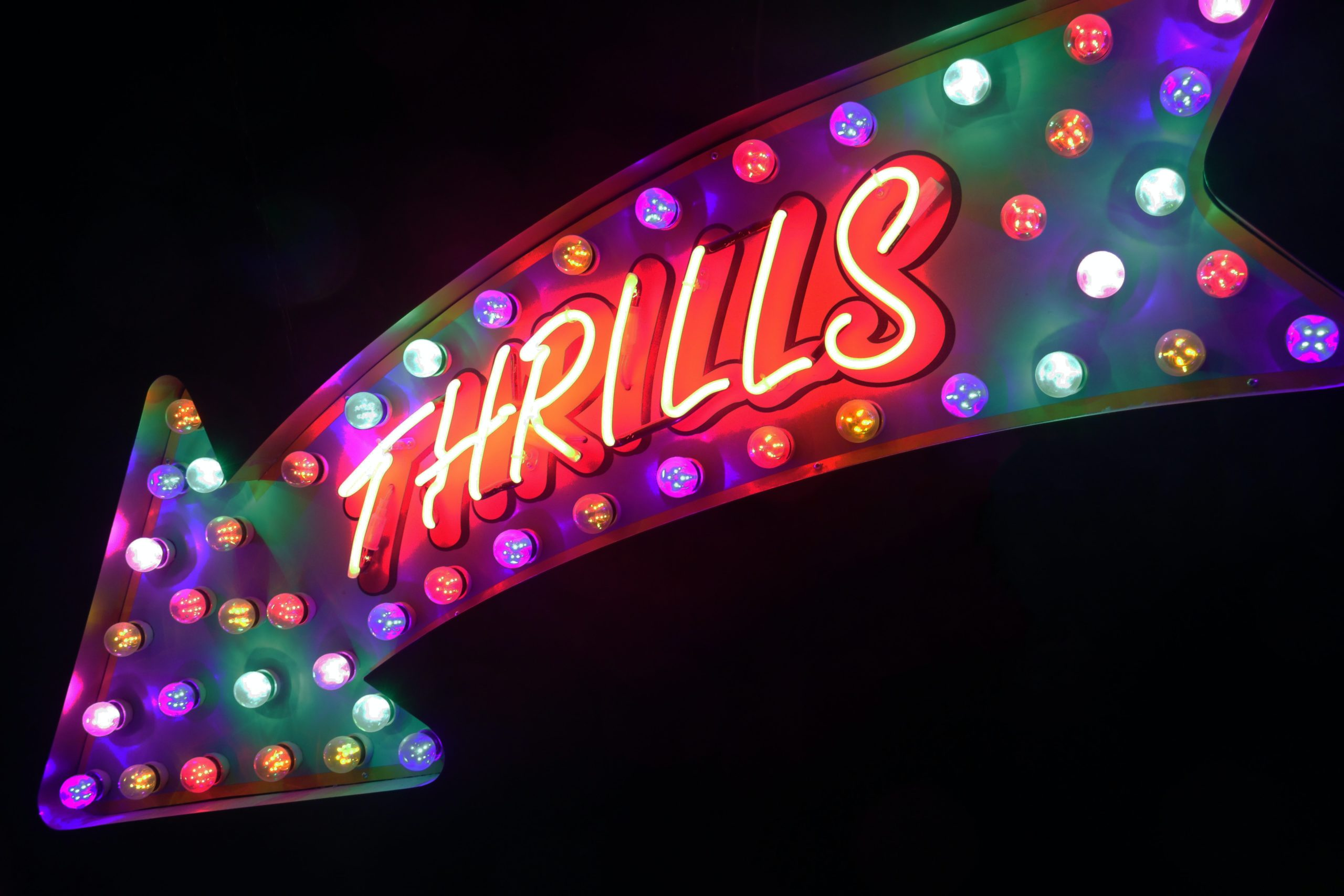 neon sign that says Thrills in an arrow.