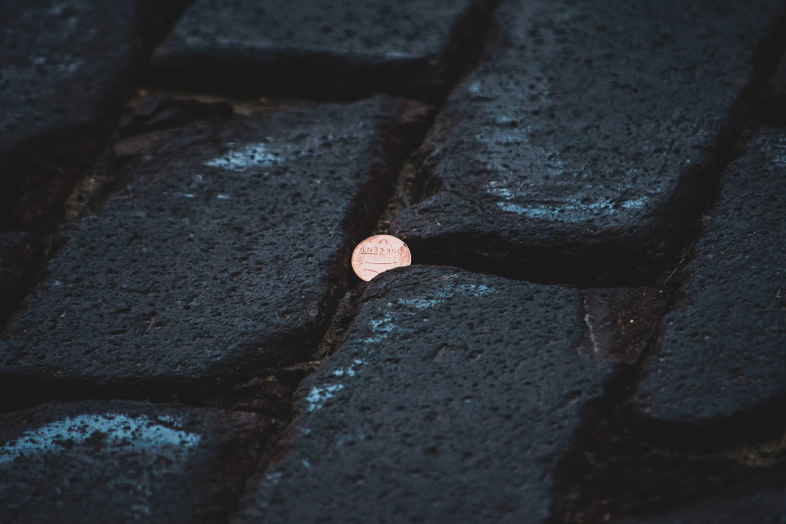 Black cobble stones with micro coin in the crack.